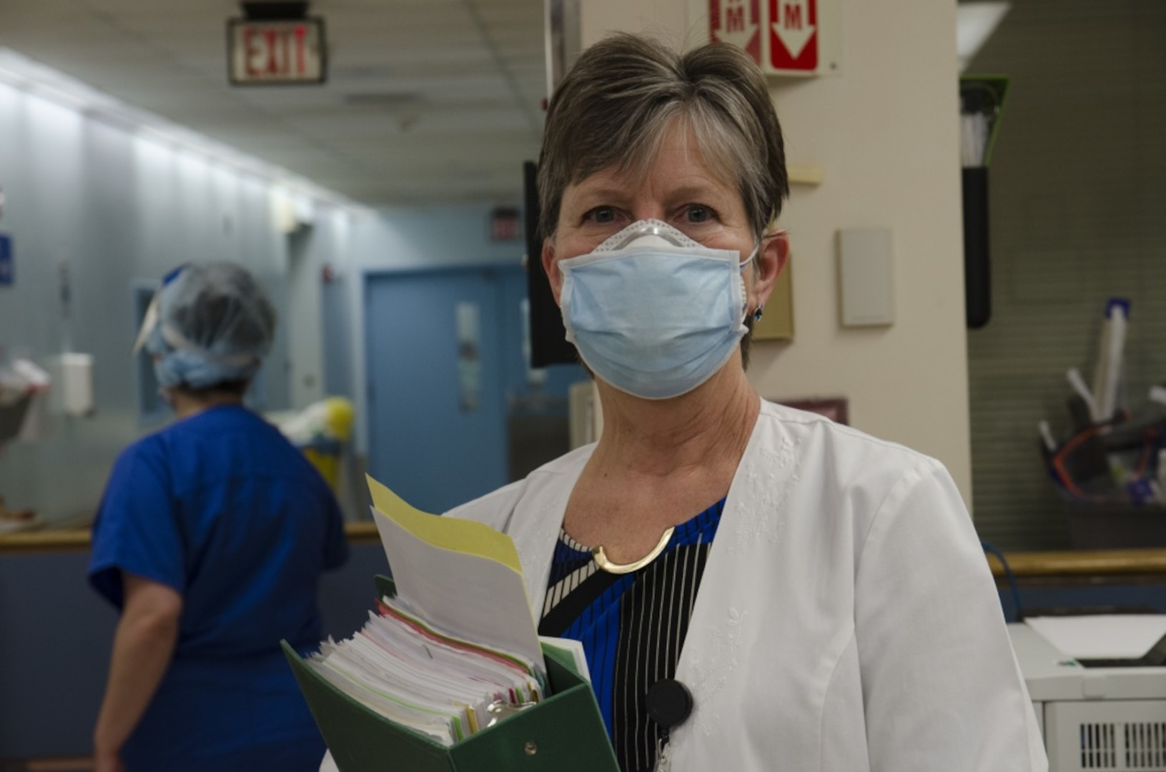 A nurse poses inside a nursing home facility while wearing a white lab coat and a face mask. She is holding a large binder full of folders and papers.