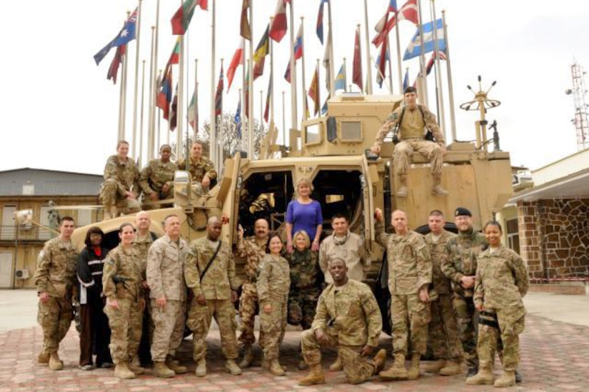 A group of people pose in front of a vehicle and a grouping of flags.