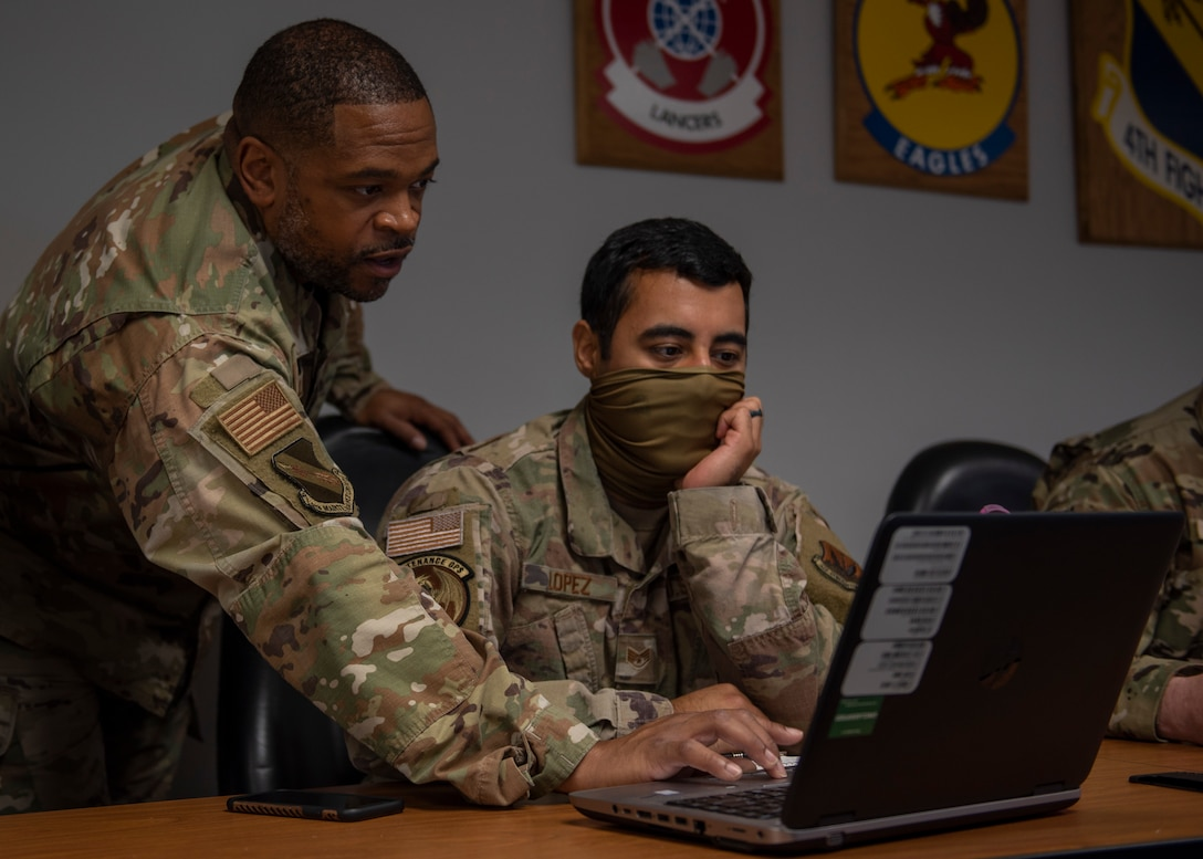Tech Sgt. Jevon Charles, 4th Fighter Readiness Squadron weapons academic instructor (left), teaches Staff Sgt. George Lopez, 4 FRS aircraft maintenance qualifications program instructor (right), how to use formulas in Microsoft Excel at Seymour Johnson Air Force Base, North Carolina, Nov. 2, 2020.