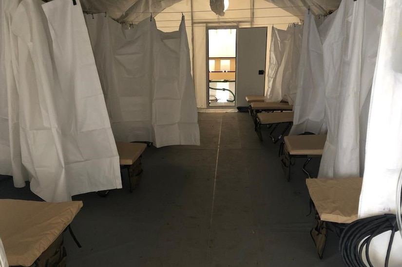 The interior ward of a field hospital is shown.