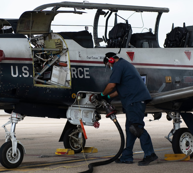 Javier Martinez Jr, 47th Flying Training Wing Maintenance aircraft worker, refuels a Texan T-6 II on the flight line, on Nov. 9 2020, Laughlin Air Force Base, Texas. He is utilizing the new commercial 3K refueler vehicle that is being tested. (U.S. Air Force photo by Airman 1st Class David Phaff)