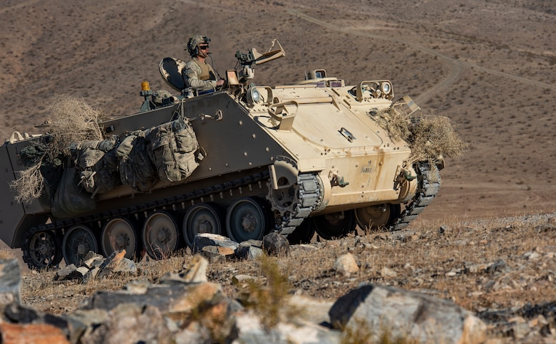 Soldier drives Armored Personnel carrier on hill.