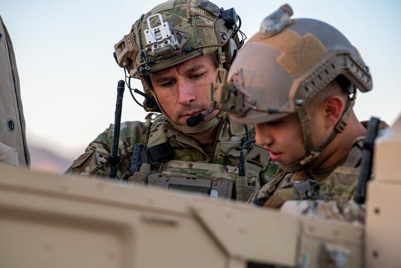 Airman look down at a Humvee.
