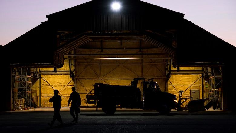 Airmen walk in front of barn at night.