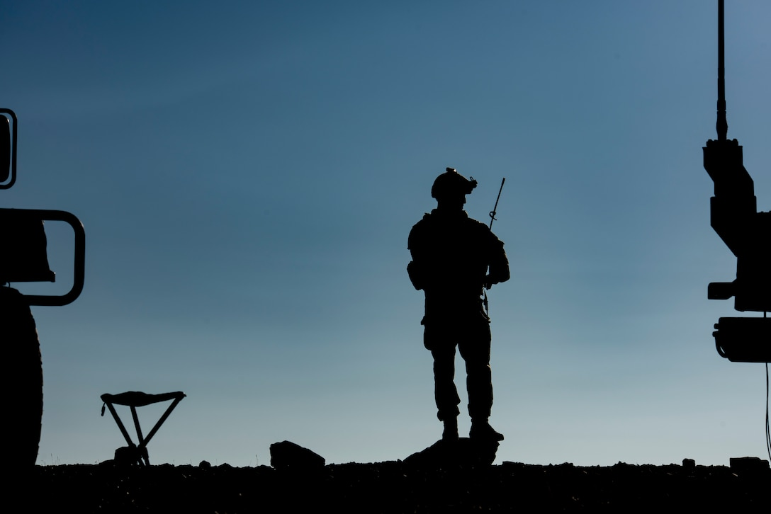 Airman stands on a hill and talks on the radio.