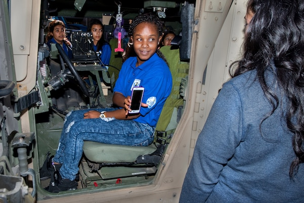 A young girl sits inside a military vehicle.
