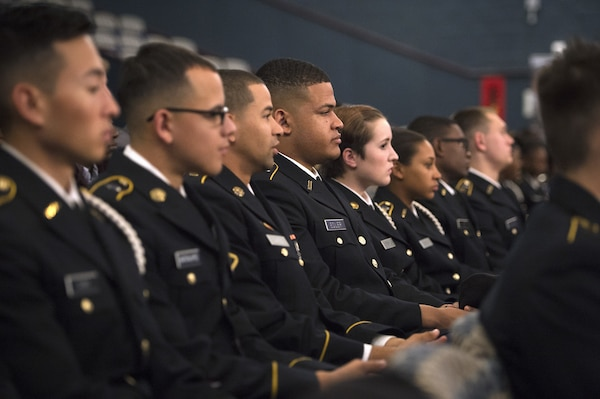 Students in military uniforms sit in rows in an auditorium.
