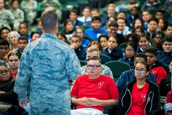 Young students sit in rows in an auditorium and listen to a military officer speak.