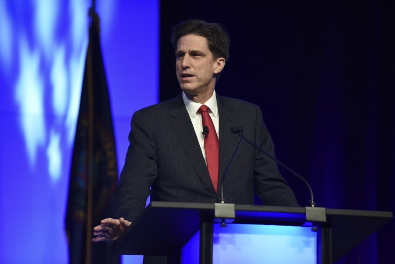 A man in a business suit stands at a lectern.