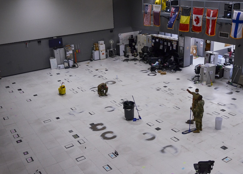 U.S. Air Forces Central Airmen from the Combined Air Operations Center, Al Udeid Air Base, Qatar, sweep and mop the newly emptied operations floor before renovations Oct. 26, 2020.