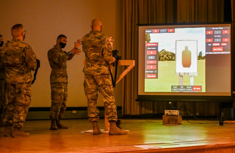 Technical Sgt. Israel Navarro (middle), 729th Air Control Squadron, demonstrates a laser-based, dry fire weapons training system Nov. 6, 2020, at Hill Air Force Base, Utah for Chief Master Sgt. Aron Garrard (right), 388th Maintenance Squadron, Nov. 6, 2020 at Hill Air Force Base, Utah. Airmen in 729th ACS are using the system for training to help them weapons qualify before deployments.  (U.S. Air Force photo by Cynthia Griggs)