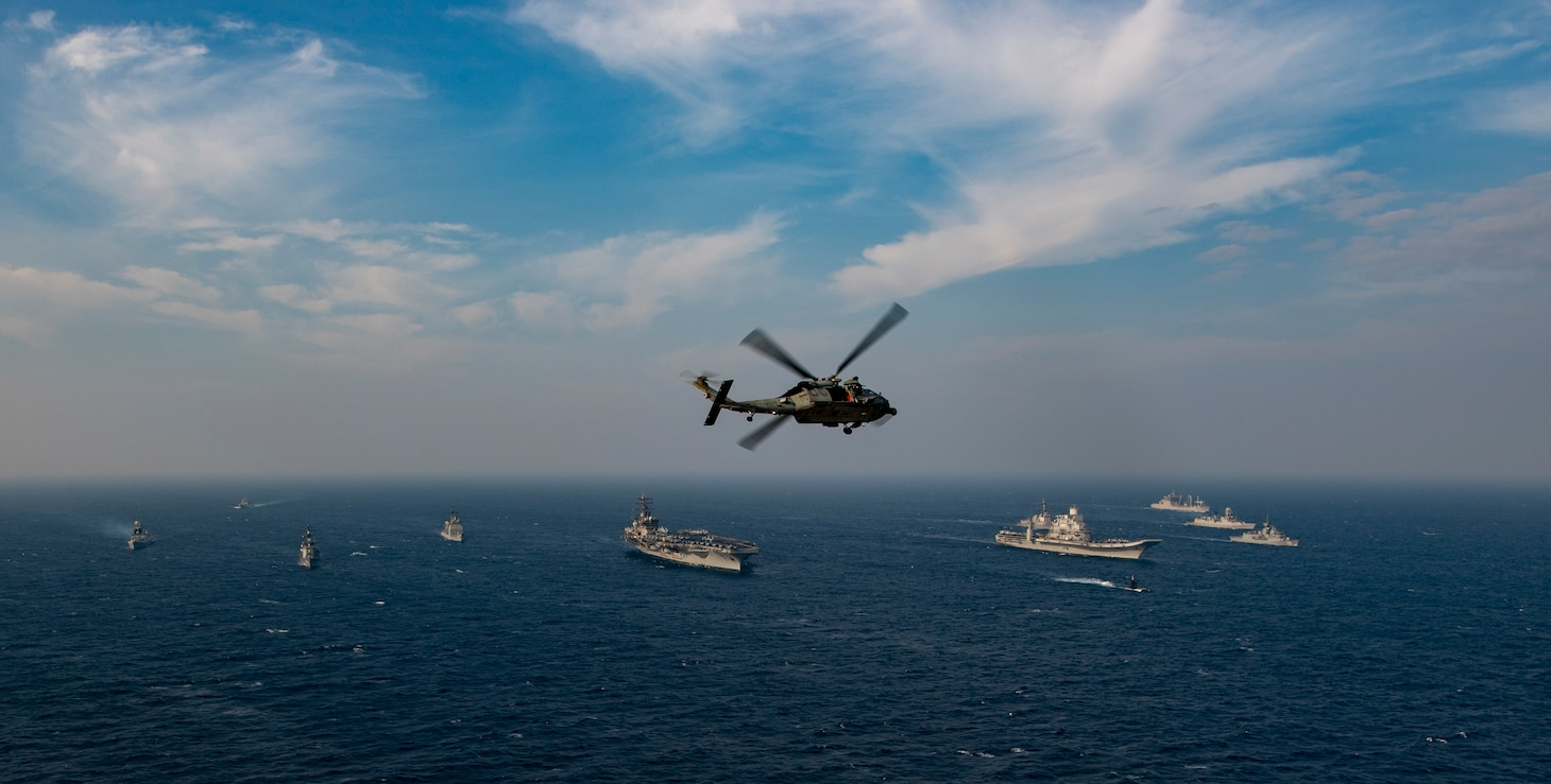 An MH-60S Sea Hawk helicopter flies over ships from the Indian navy, Japan Maritime Self-Defense Force (JMSDF), the Royal Australian navy and the U.S. Navy as they sail in formation.