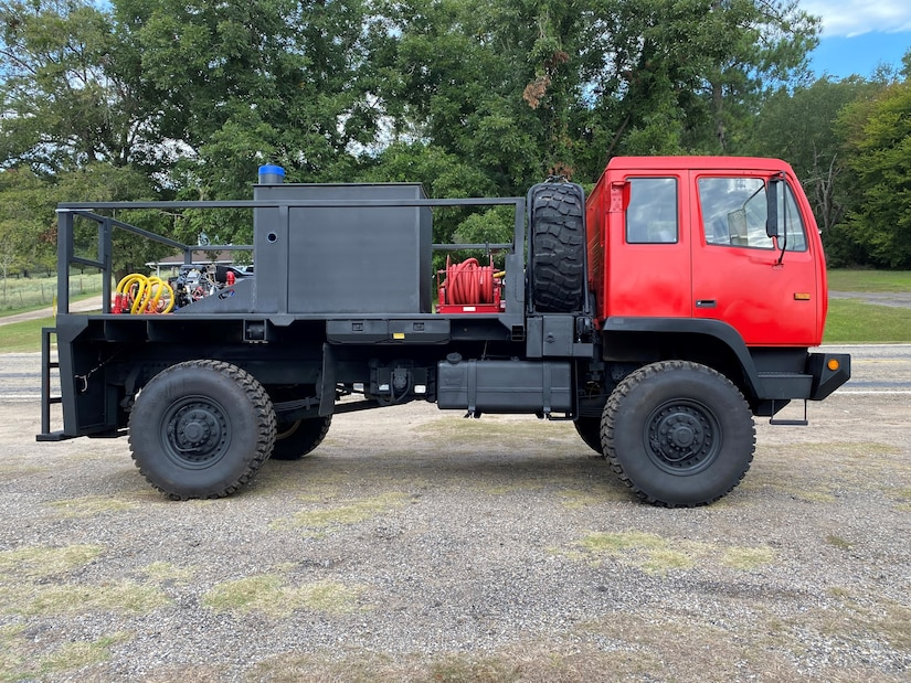 Side view of a former military truck now converted to help fight fires with a tank and pump unit added to the bed behind the cab.