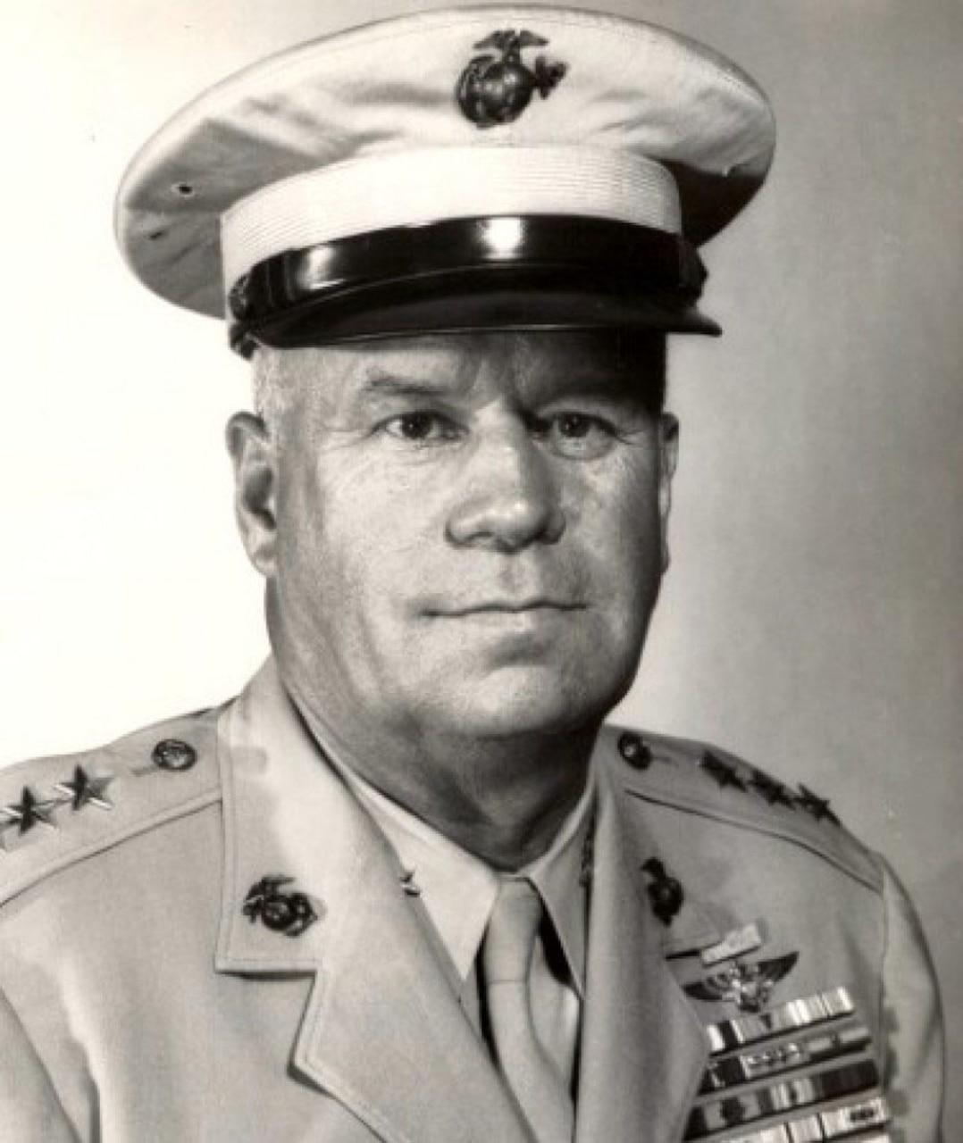 A man in uniform looks toward a camera.