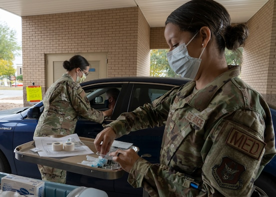 Photo of Airmen next to truck preparing flu vaccines