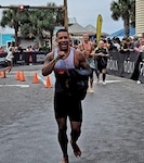 Raul Garcia, a Defense Logistics Agency Energy Customer Account Specialist, runs during his transition from the 2.4-mile open ocean swim to his bike where he'll begin the 112-mile bicycle ride before the final event, a 26.2-mile run. Garcia completed his first Ironman triathlon in Panama City, Florida, Nov. 7, 2020, in just over 14 hours.