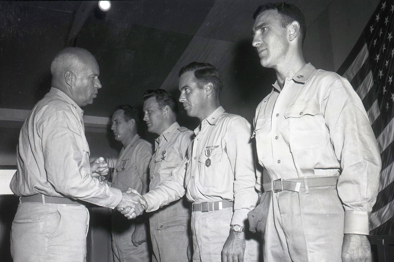 A man shakes the hand of a man facing him, who is lined up beside three other men.