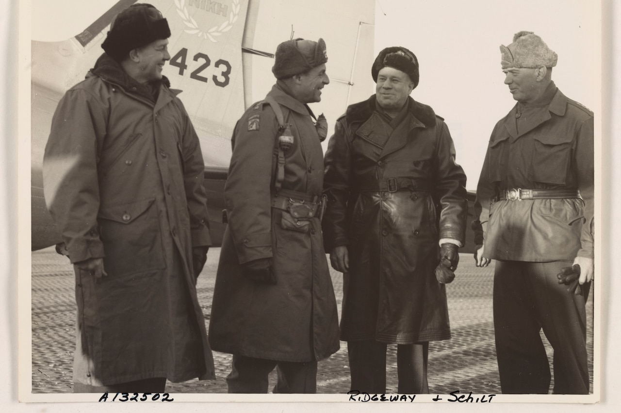 Four men in winter garb stand beside the tail of an airplane.