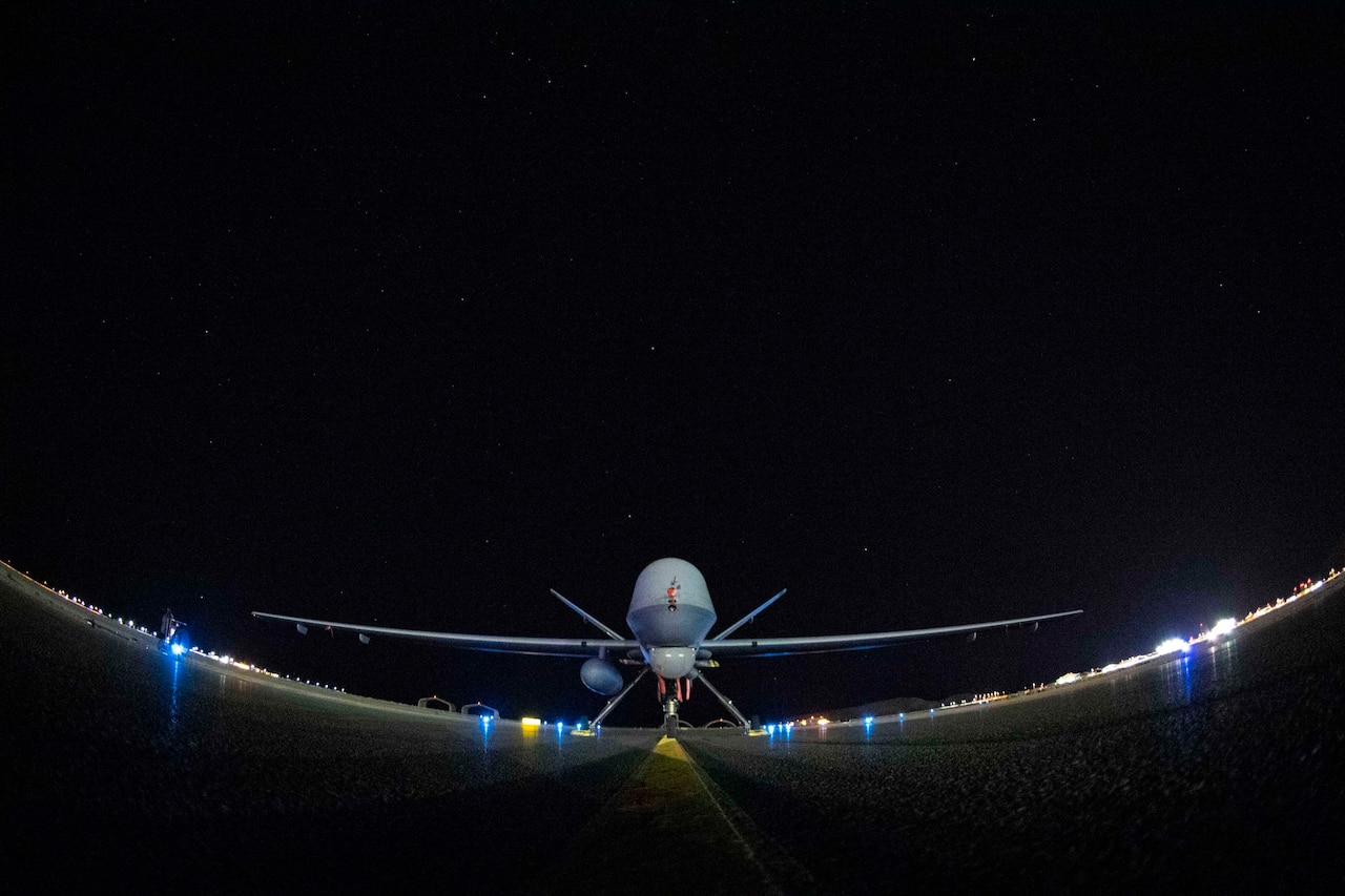 An Air Force unmanned aerial vehicle sits parked at night.
