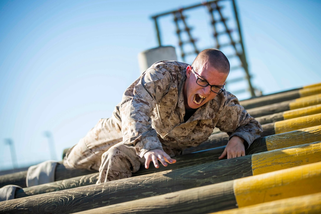 A Marine Corps recruit climbs over a wooden obstacle.