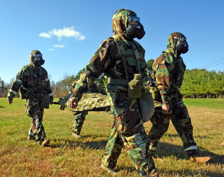 Participants transport a mock patient while wearing Mission Oriented Protective Posture gear during MEDEVAC tactical combat casualty care training at the Babe Ruth field, Nov. 16, 2020 on Joint Base McGuire-Dix-Lakehurst, N.J. Airmen must wear personal protection equipment while performing MEDEVAC tasks to practice safety procedures and prevent further casualties. (U.S. Air Force photo by Daniel Barney)