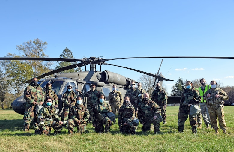 Participants pose in front of a UH-60 Blackhawk helicopter before initiating MEDEVAC tactical combat casualty care training at the Babe Ruth field, Nov. 16, 2020 on Joint Base McGuire-Dix-Lakehurst, N.J. The objectives of MEDEVAC TCCC are to treat casualties, prevent additional casualties and mission completion. (U.S. Air Force photo by Daniel Barney)