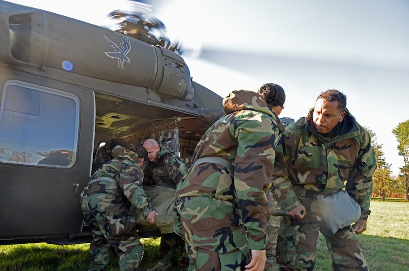 Service members transport a patient out of a helicopter.