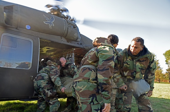 During MEDEVAC training, participants prepare to transport a mock patient out of a UH-60 Blackhawk helicopter at the Babe Ruth field, Nov. 16, 2020 on Joint Base McGuire-Dix-Lakehurst, N.J. This training helps military personnel on how to transport patients in and out of moving vehicles. (U.S. Air Force photo by Daniel Barney)