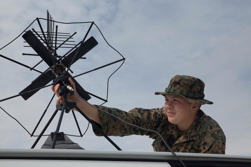 A service member adjusts a satellite communications device.