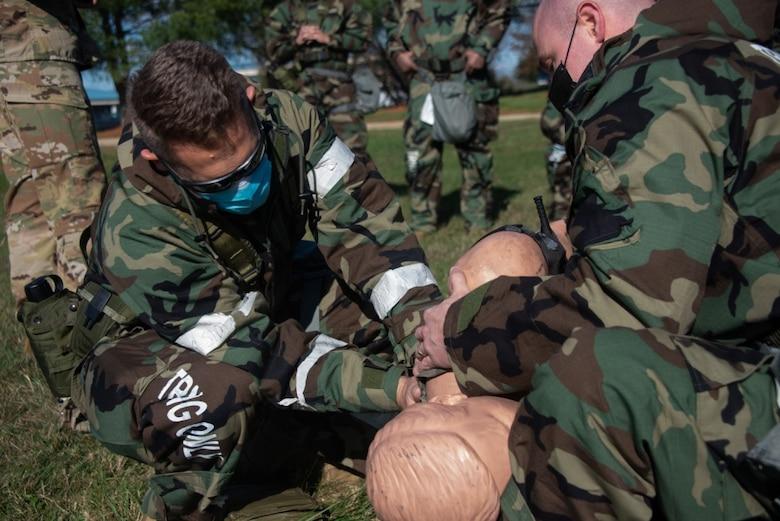 Airmen set a patient on a litter.
