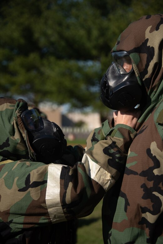 Airmen check each other's protective gear.