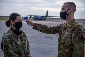 An Airman takes the temperature of another Airman in front of a C-130.