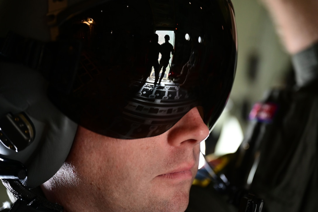 A loadmaster watches as jumpmasters prepare jumpers to jump out of a C-130J Super Hercules.