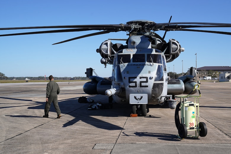 U.S. Marine Corps Sgt. Samuel Bonita, Marine Heavy Helicopter Squadron 464 aerial observer, Marine Corps Air Station New River, North Carolina, observes a Sikorsky CH-53E Super Stallion on the flightline at Keesler Air Force Base, Mississippi, Nov. 17, 2020. Marines came to Keesler to conduct routine training operations in and around the Mississippi area. (U.S. Air Force photo by Airman 1st Class Seth Haddix)