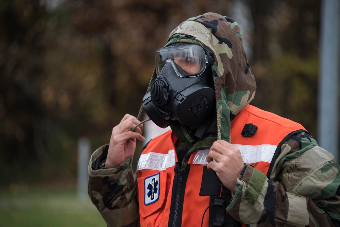 U.S. Air Force Staff Sgt. Joseph Lindgren, 52nd Dental Clinic technician, puts on chemical training gear before assisting with patient decontamination during an exercise at Spangdahlem Air Base, Germany, Nov. 17, 2020. Exercise mock patients are decontaminated before being moved into the medical clinic for further treatment. (U.S. Air Force photo by Senior Airman Chance D. Nardone)