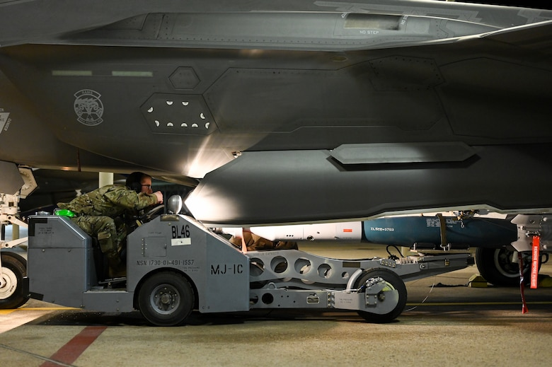 A photo of maintainers loading weapons onto and F-35A Lightning II.
