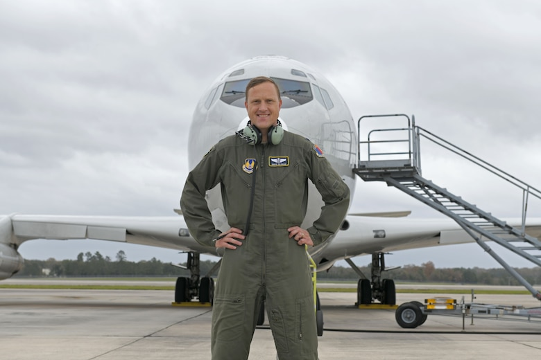 Photo shows man standing in front of aircraft.