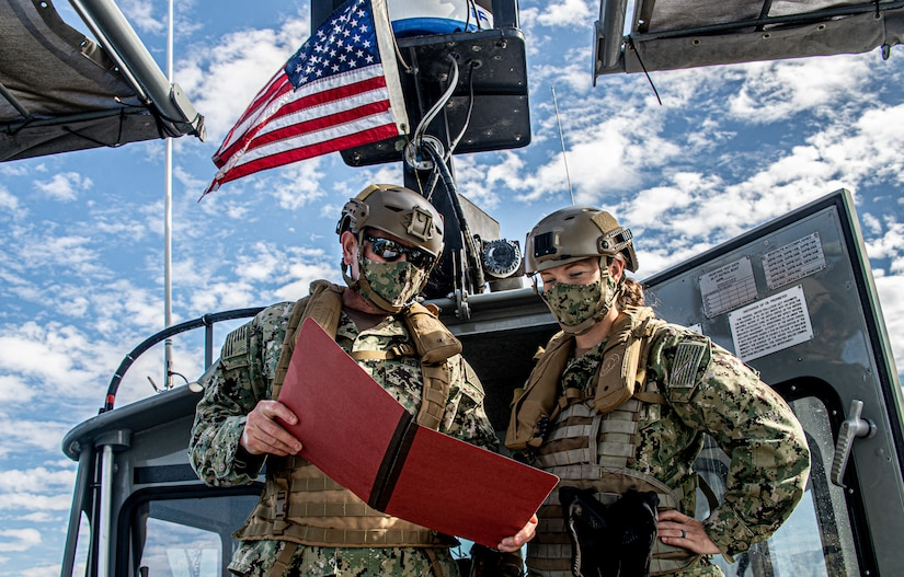 Training officer, on left, assigned to Maritime Expeditionary Security Squadron 11, briefs squadron's chief staff officer and executive officer aboard 34-foot Sea Ark patrol boat during navigation check ride exercise off coast of Long Beach, California, November 12, 2020 (U.S. Navy/Nelson Doromal, Jr.)