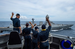Sailors aboard USS Sterett (DDG 104) wave to the crew of the Indian navy destroyer INS Kolkata (D 63) during Malabar 2020.