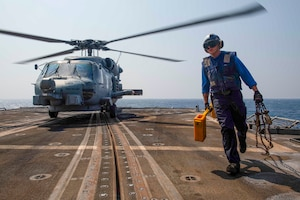 Boatswain�s Mate Seaman Elijah Parra, from Anchorage, Alaska, clears the rotor arc of an Royal Australian navy MH-60 Sea Hawk helicopter after removing chocks and chains