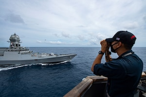 A Sailor uses a laser range finder to monitor the distance between the Indian navy destroyer INS Kolkata and the guided-missile destroyer USS Sterett (DDG 104) during Malabar 2020.