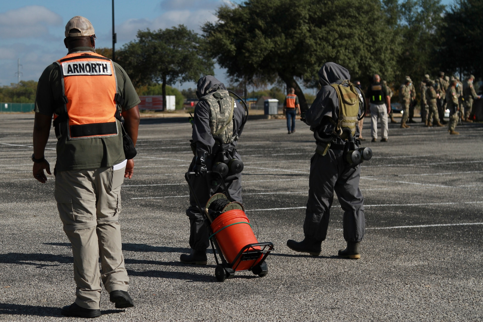 Gerald Evans (left), an observer controller contractor for U.S. Army North Civil Support Training Activity, evaluates Pfc. Wenhui Huang (center), a chemical, biological, radiological and nuclear specialist, and Pfc. Jayson Morris-Dunlap (right), a signal support systems specialist, both assigned to the 181st CBRN Company, as they set up force protection measures during a mass casualty decontamination lane at the Nelson W. Wolff Municipal Stadium Nov. 5.