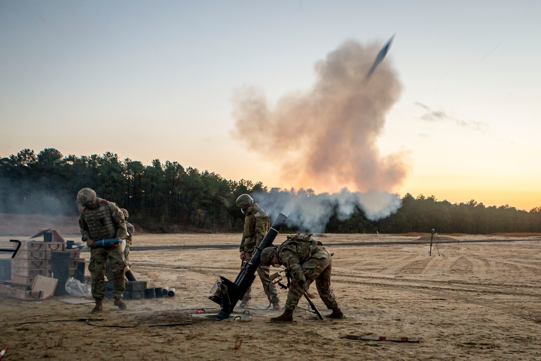 Soldiers fire a weapon in a field.