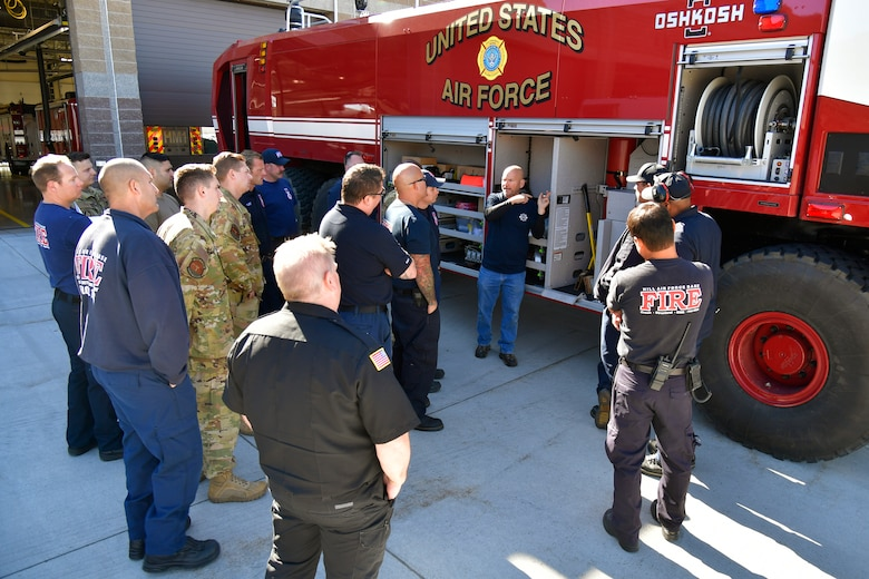 Firefighters and others standing around the crash/fire response vehicle.