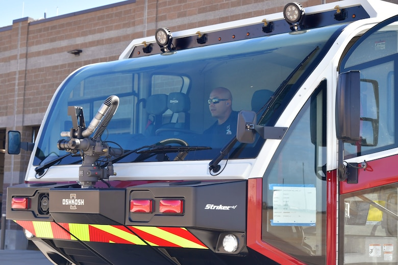 A firefighter sits in the cab of a new crash/fire response vehicle.