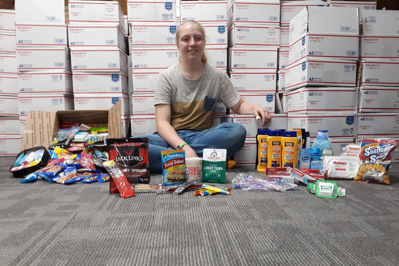 A girl poses with a care package.
