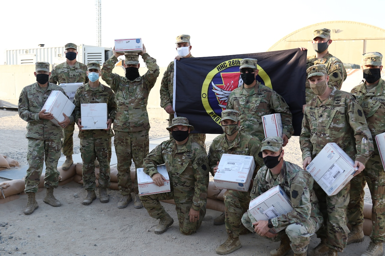 Soldiers pose with care packages.