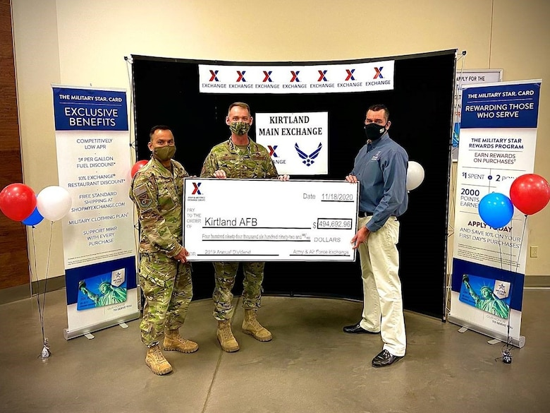 three men holding a large check