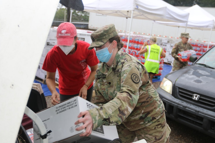 Spc. Josie Staples, 690th Chemical Biological Radiological Nuclear (CBRN) Company from Mobile, Ala., hands out Meals, Ready to Eat to a local citizen affected by Hurricane Sally in Fairhope, Ala. on September 19, 2020. (Alabama Army National Guard Photo by Sgt. Eric Roberts)