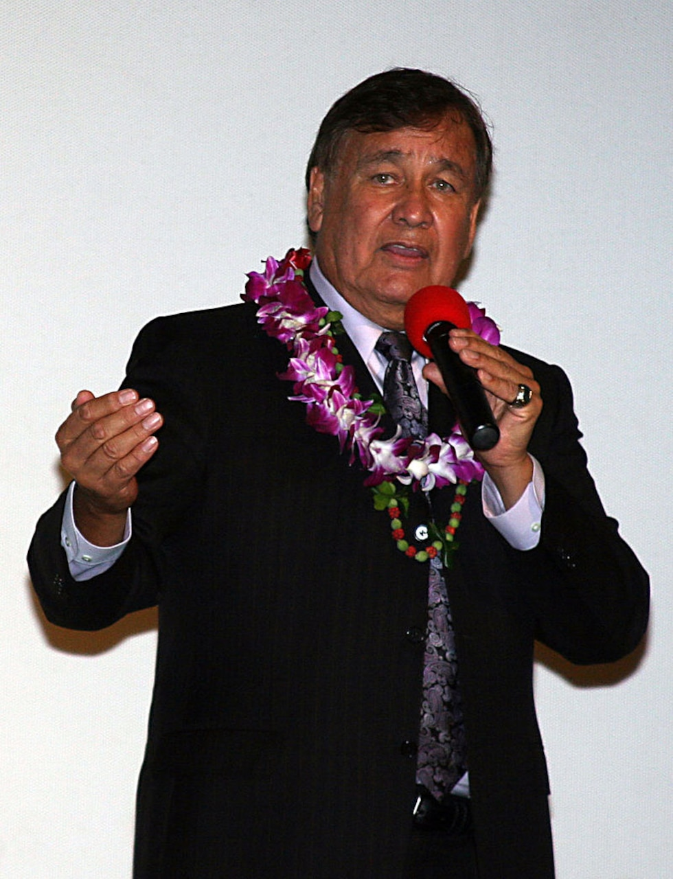 A man in business attire with a lei around his neck speaks into a microphone.